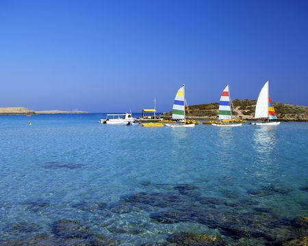 shallow water: Bright pleasure sailboats by rocks in the shallow water of Nissi Beach, Cyprus Stock Photo