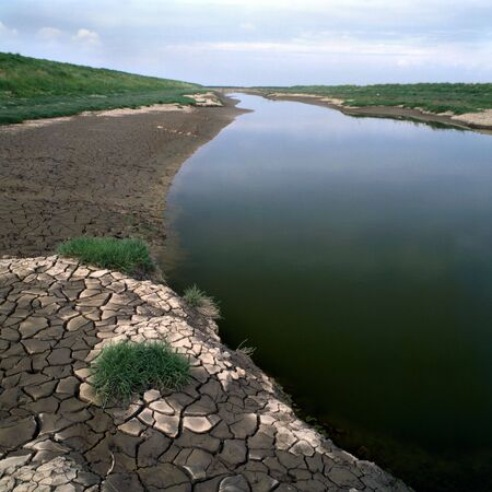 river bed: An almost dry river bed with ctacked earth by the sides