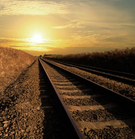Rail track going into infinity with the sun setting photo