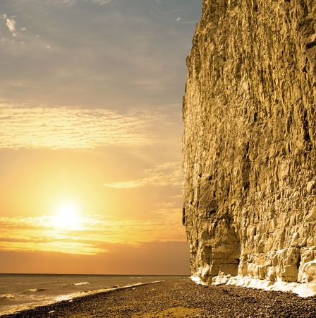 Sun setting at the coast whit large chalk cliff photo