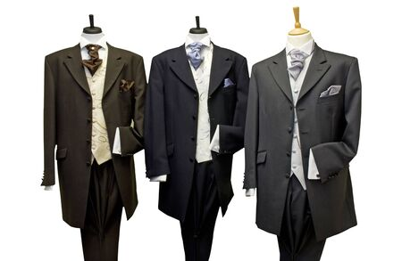 Three tailors dummies dressed in suits and standing in a line.