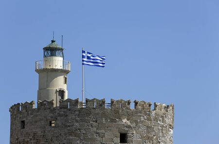 greek flag: Fort of Saint Nicolas, Mandraki harbour, Rhodes, Greece Stock Photo