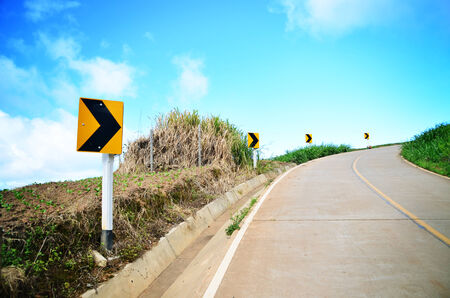 curvaceous: Curve road sign on down hill.