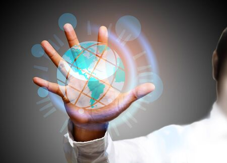 connected world: Global Communication - A businessman holding a glowing, connected, World. Stock Photo