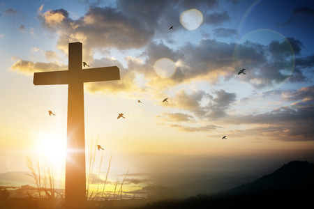 cross on blurry sunset background . Stock Photo