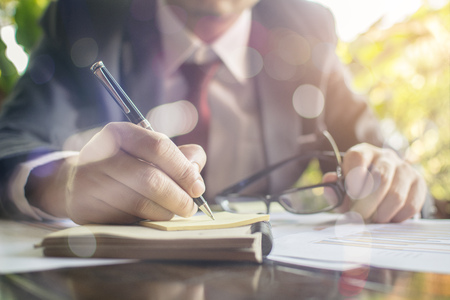 Businessman check seriously analyzes a financial reports and writing on notebook on wooden table at office  Finance managers task Concept business and finance