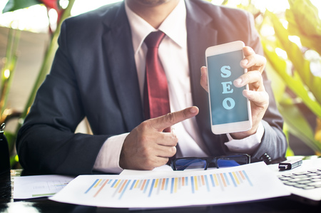 Businessman pointing at a telephone.seo concept. Stock Photo