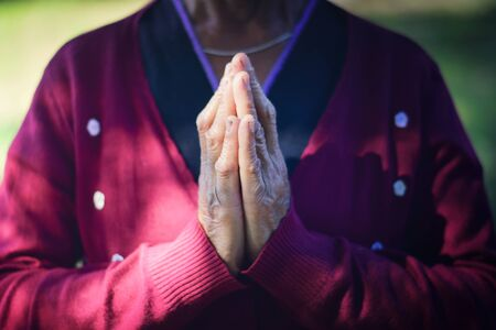 The old woman closed hand is prayer and thank God.