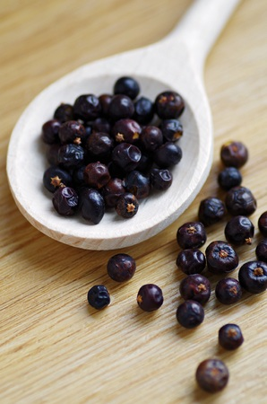 enebro: Juniper. Juniper berries. Organic juniper berry on wooden background. Organic spices in wood spoon on a wooden background.