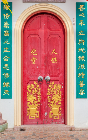 east gate: Old red chinese temple door with crave leaf