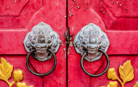 Old red chinese temple door with crave leaf photo