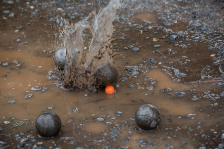 Petanque steel balls in mud.