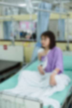 Broken arm patient with arm sling for treatment in the hospital blurred.