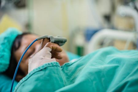 Paciente con sensor de saturación de oxígeno en el pulsioxímetro del hospital. Foto de archivo