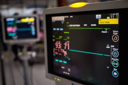 Modern vital sign monitor on patient background at ward in the hospital.