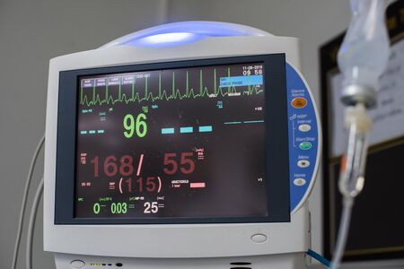 Modern vital sign monitor on patient background at ward in the hospital. Imagens