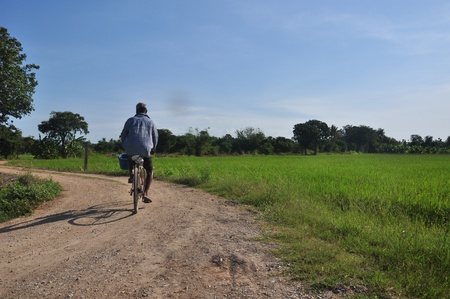 The old man ride bicycle on country road photo