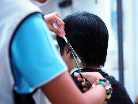 man haircut: Professional barber making stylish man haircut