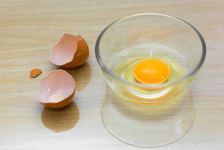 egg in bowl and eggshell on wood background