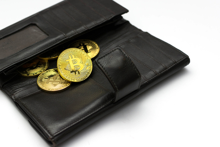 Golden bitcoins on black wallet, Digital symbol of a new virtual currency with white background. Stock fotó