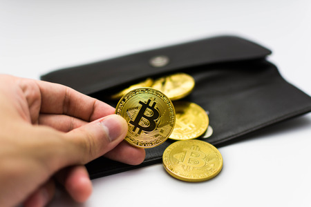 Golden bitcoins in hand. Digital symbol of a new virtual currency on white background and black wallet. Stock fotó