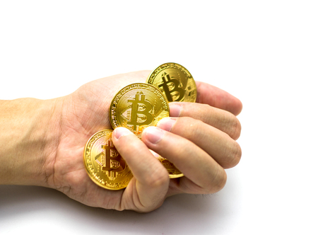 Golden bitcoins in hand. Digital symbol of a new virtual currency on white background.
