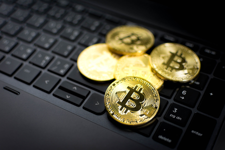 Golden Bitcoins on computer keyboard background.
