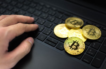 Golden Bitcoins and hand on computer keyboard background. Stock fotó