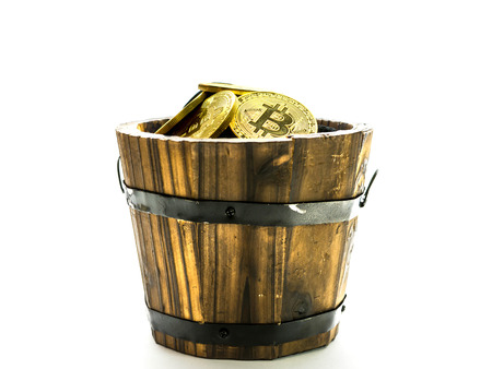 Golden Bitcoins in barrel. Digital symbol of a new virtual currency on isolate background.