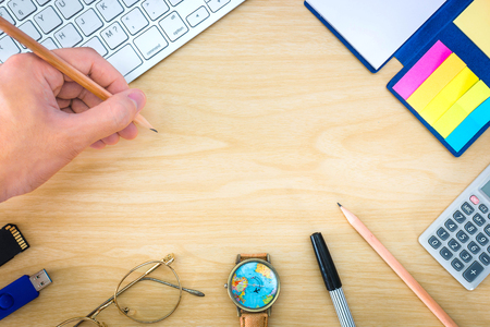 Top view, Hand holding a pencil over office desk with notepad, calculator, glasses and watch, copy space.