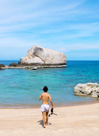 The tourist holding the snorkel in front of The stone in blue sea with clear blue sky at Koh Chang island in Thailand