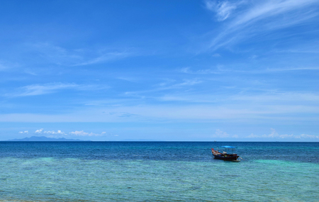 The boat float over the blue sea at Koh Chang island in Thailand with clear blue sky