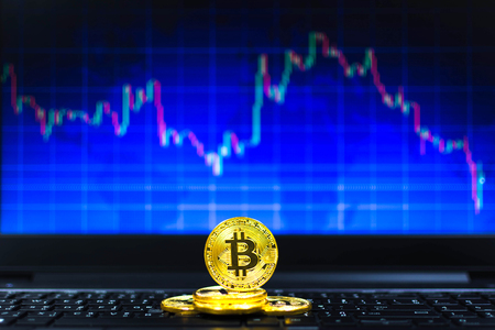 gold bitcoins on key board and BTC trading chart in background, Financial concept Stock fotó