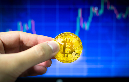 Man holding gold bitcoin and BTC trading chart in background, Financial concept Stock fotó