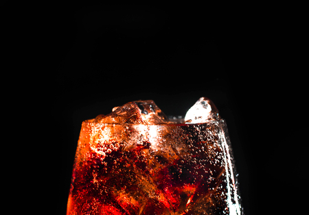 Cola and ice in a glass on black background. Stock fotó