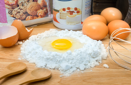 flour with egg and ingredients for homemade bakery on wooden background