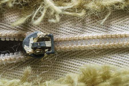 Close-Up Of Old Zipper Surrounded By Olive Green Fibers In Pattern