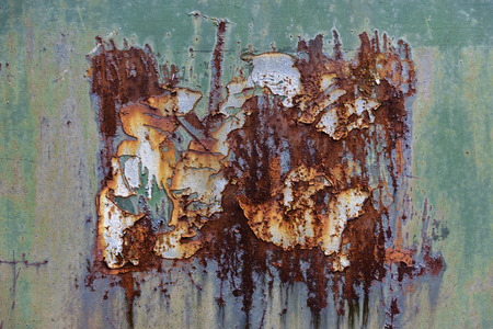 Close-Up Of Crumbling Green And White Paint Peeling Off From A Rusty Metal Wall Stock Photo