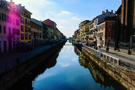 milánó: Scenic View Of The Crowded Naviglio Grande District In Milan With Water Reflections And Purple Sun Flare Against Blue Sky