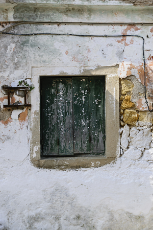 windows frame: Old Wooden Greek Traditional Window With Green Paint And Ripped Pieces Of Paper On Crumbling Facade