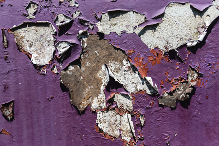 Close-Up Of Violet Wall With Cracking Layers Of Paint