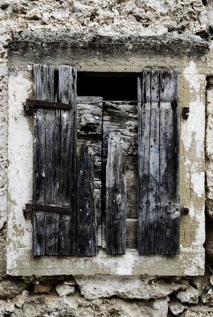 windows frame: Old Rotten Greek Traditional Wooden Window With Missing Boards And Rusty Staples Stock Photo