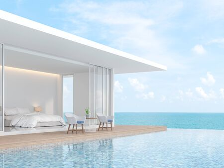 A white villa in minimal style with a sliding open overlooking the bedroom. In front of the bedroom is a wooden balcony and swimming pool. That overlooks the sea - 3d render Foto de archivo