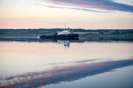 Tug pulls a barge on the river Severnaya Dvina Archivio Fotografico