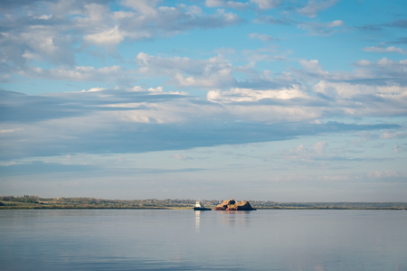 A small tug pulls a barge laden with wood along the river Severnaya Dvina
