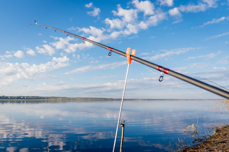 The abandoned feeder rod in a summer day on the river Northern Dvina