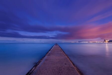 Sunrise over a jetty in Waikiki, Hawaii photo