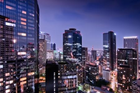 밤에 도쿄의 고층 빌딩 유리