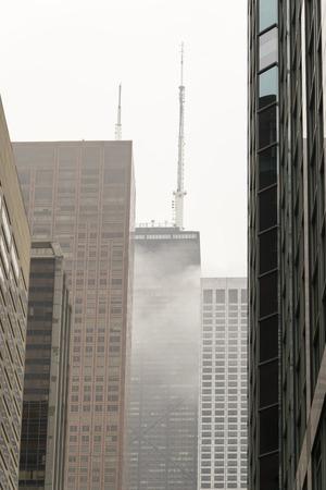 envelops: The fog envelops the skyscraper Stock Photo