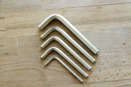 chrome vanadium: Set of five chrome vanadium allen screw supported on a wooden table Stock Photo